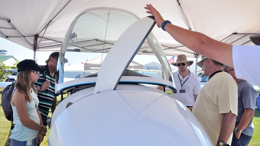 AirVenture attendees look at the Stemme S12 motorglider's cockpit. A Stemme dealership representative holds a propeller blade in the extended position; the blades retract when the engine is shut off.