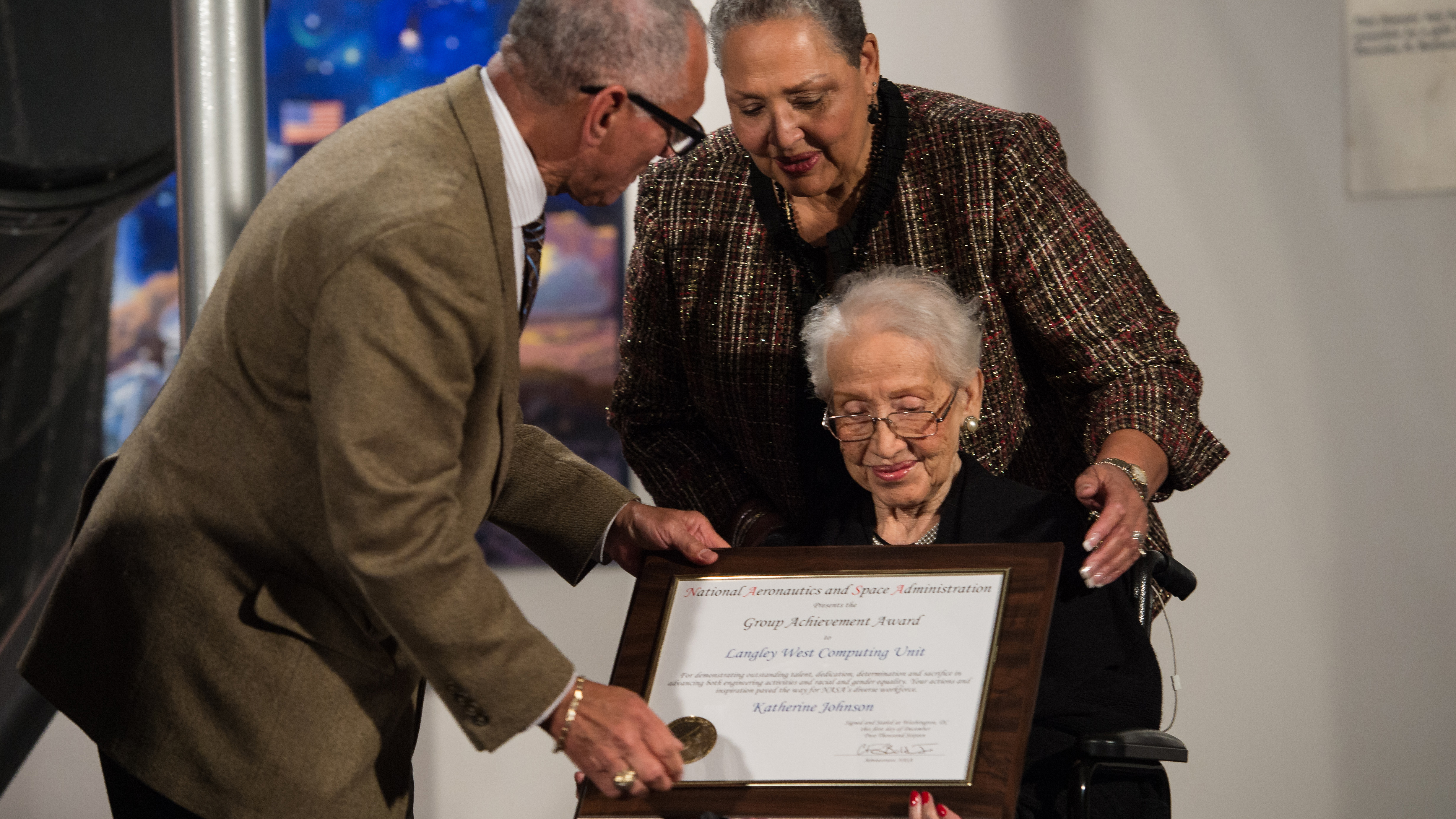NASA Administrator Charles Bolden presents an award to Katherine Johnson, the African American mathematician, physicist, and space scientist, who calculated flight trajectories for John Glenn's first orbital flight in 1962, at a reception to honor members of the segregated West Area Computers division of Langley Research Center on Thursday, Dec. 1, 2016, at the Virginia Air and Space Center in Hampton, VA. Afterward, the guests attended a premiere of 'Hidden Figures' a film which stars Taraji P. Henson as Katherine Johnson, Octavia Spencer as Dorothy Vaughan, and Janelle Monae as Mary Jackson. Photo Credit: (NASA/Aubrey Gemignani)