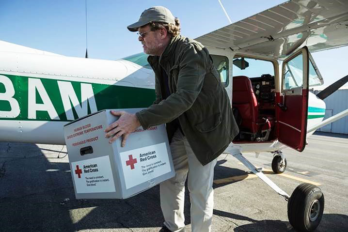 Flight instructor Chris Irwin unloads a box of American Red Cross supplies from the Glendale Community College airplane he had flew in from Whiteman Airport in Los Angeles. Photo courtesy of the Disaster Airlift Response Team.