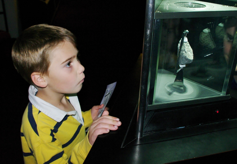 A young visitor gazes at a Moon rock at the Cosmosphere in Hutchinson, Kansas. Photo courtesy Kansas Tourism.
