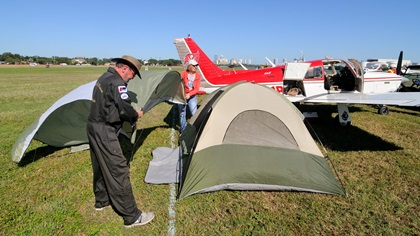 Buzz and Lori Hohmann of Zephyrhills, Florida, install the rain fly on their tent at the 2017 AOPA Tampa Fly-In. It was the first AOPA Fly-In the couple has attended. Photo by Mike Collins.