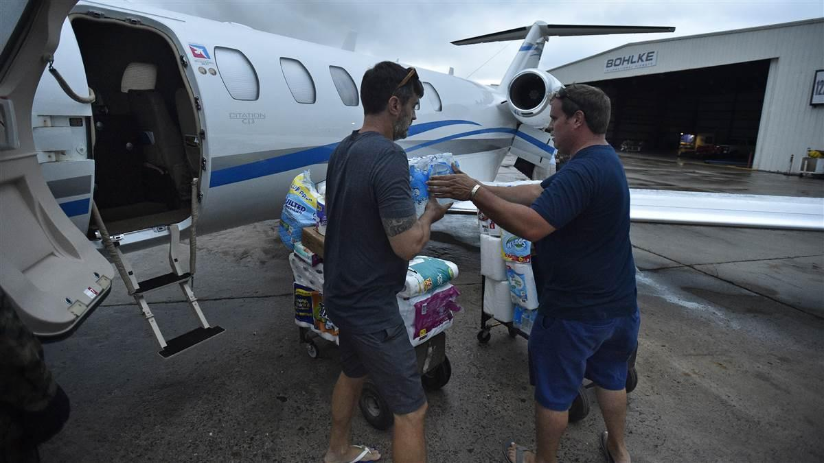 Hurricane Irma victims Steve Hookstra and Mike Keaton help unload supplies and medicine from an aircraft at the St. Croix, U.S. Virgin Islands, general aviation ramp Sept. 14. Hookstra and Keaton had attended a friend's wedding at nearby St. John before the powerful storm hit. Photo by David Tulis.