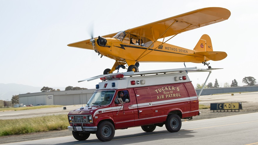 Justin Ramsier drives a 1990 ambulance while Eric Tucker pilots his J-3 Cub from a platform attached to the ambulance roof. Photo courtesy of Method Seven and Donald Beirdneau.