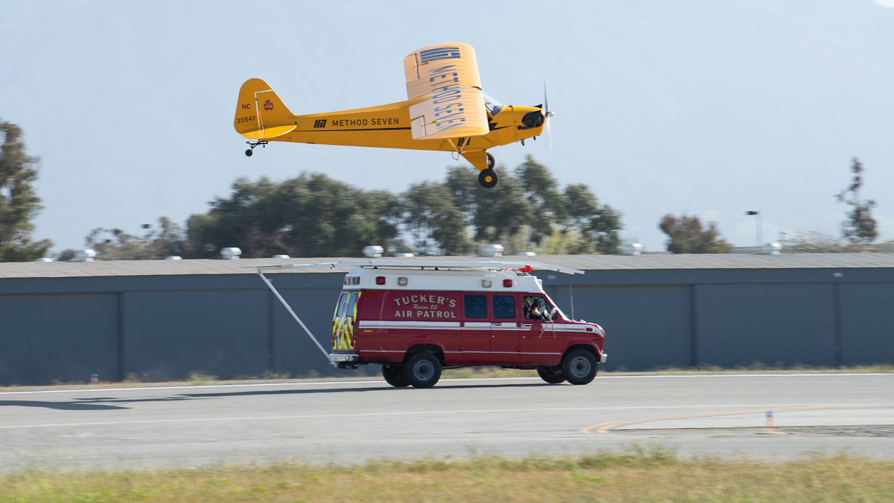 Justin Ramsier drives a 1990 ambulance while Eric Tucker practices landing his J-3 Cub on a platform attached to the ambulance roof. Photo courtesy of Method Seven and Donald Beirdneau.