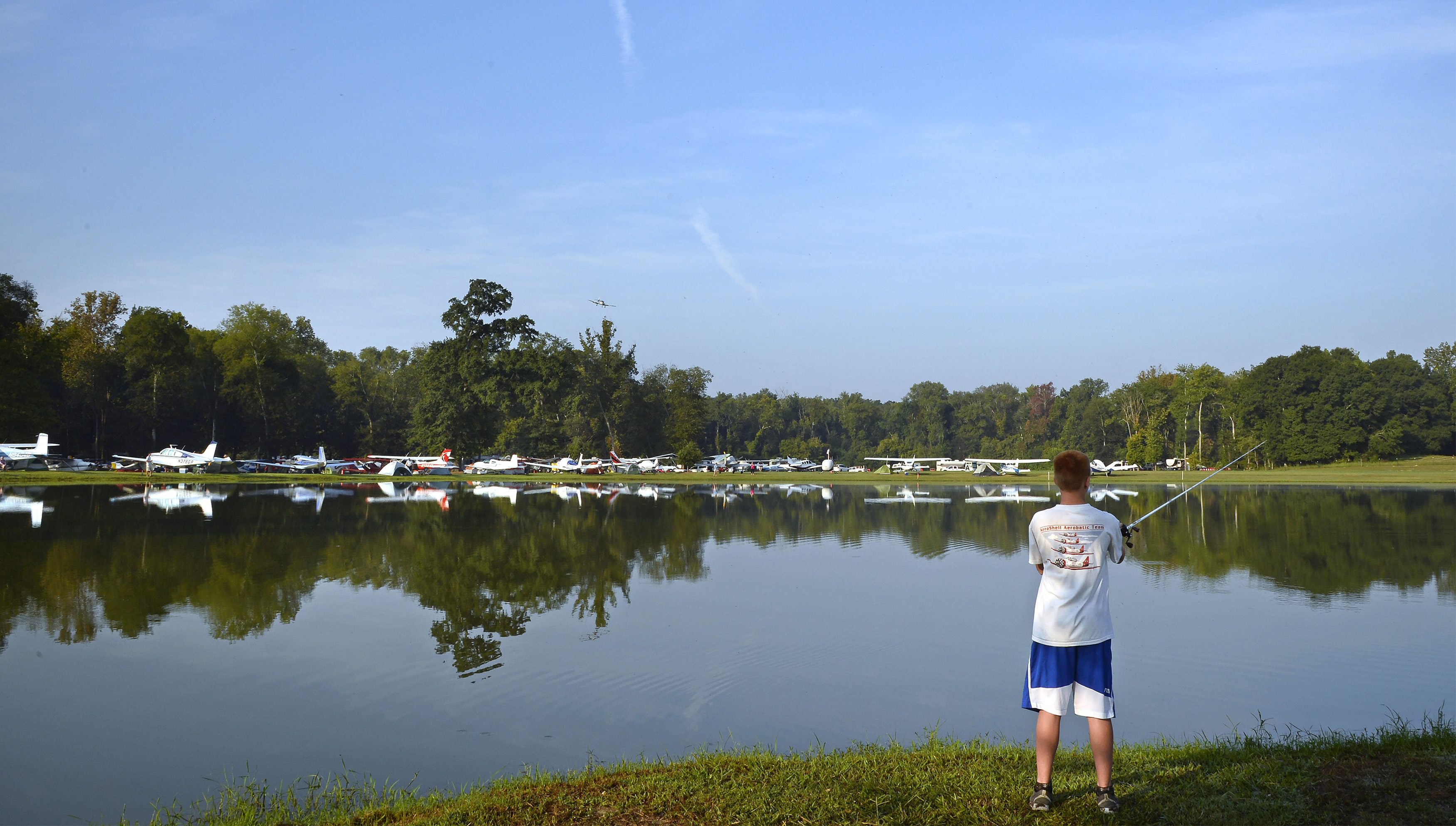Aircraft are reflected in a pond at Triple Tree Aerodrome where Kyle Carden casts for bass during the annual fly-in. Carden and his father Keith flew from their Irvington, Alabama, home in their Stinson Voyager, an airplane that is now serving the family's fourth generation. Photo by David Tulis.