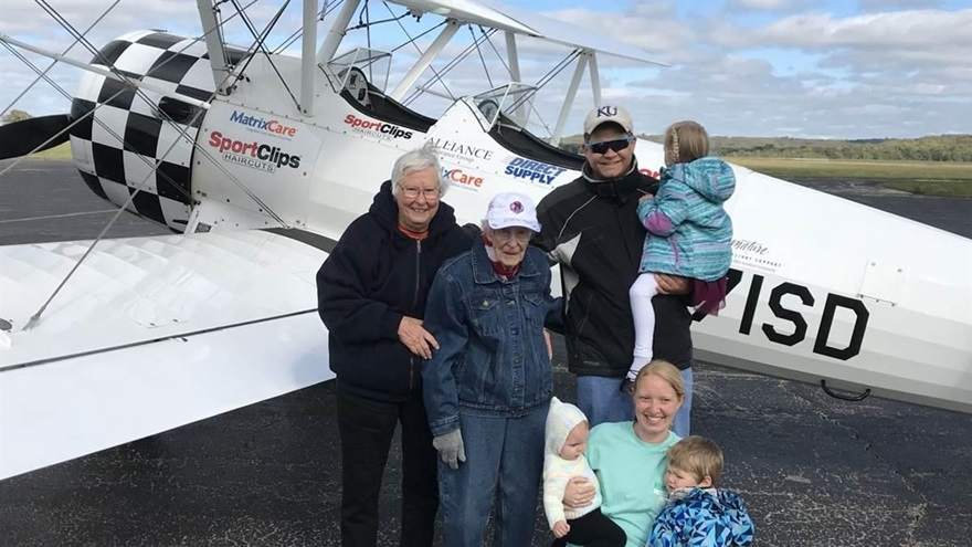 Norma Evans, age 104, poses with three generations of her family beside an Ageless Aviation Dreams Stearman. She took her second flight in the open-cockpit biplane. Photo courtesy of the Ageless Aviation Dreams Foundation.
