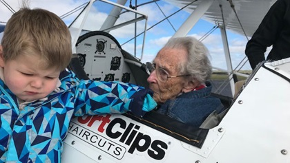 The great grandson of Norma Evans, age 104, visits his grandmother in the cockpit of a Stearman before she went flying. Photo courtesy of the Ageless Aviation Dreams Foundation.