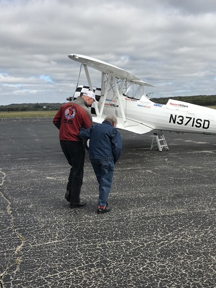 Pilot Darryl Fisher walks Norma Evans, age 104, to an Ageless Aviation Dreams Stearman for her flight. Photo courtesy of the Ageless Aviation Dreams Foundation.