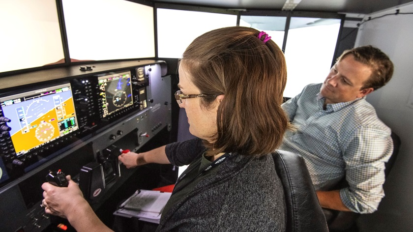 Josh Harnagel, Redbird vice president of marketing, shows Sarah Deener the Redbird Guided Instrument Flight Training (GIFT) IFR training program. Photo by Mike Collins.