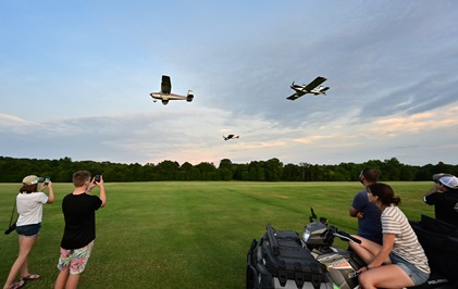 Young aviators capture the moment as a flight of three aircraft make a low approach during sunset flights above the 7,000-foot-long grass landing strip. Photo by David Tulis.