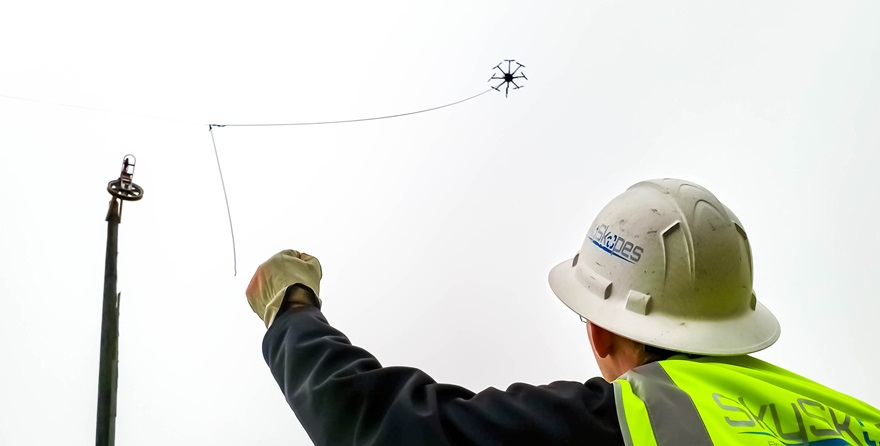 "During a line string, SkySkopes employee Cory Vinger relays information using hand signals to the drone pilot flying the ""line bird,"" in this case a FreeFly Alta 8. Photo courtesy of SkySkopes."