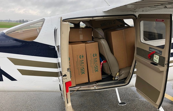 A Cessna 206 is loaded with boxes of medical face shields before Michigan Seaplane flight school instructors Nick Hall and Mike Mato depart from Indiana where the protective devices were manufactured. General aviation efforts from flight school owner Cran Jones enabled the pilots to ferry 6,000 protective plastic shields to Michigan hospitals. Photo courtesy of Nick Hall and Mike Mato.