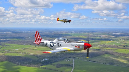 "Lou Horschel's North American P–51 Mustang, ""Mad Max,"" flies with the National Warplane Museum's Douglas C–47A near Bristol, New York, during Operation Thanks from Above. A Van's Aircraft RV–10 photo ship flown by Dan Maloney documents the event. Photo by Tetamore Photographic."