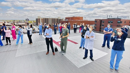 Wearing masks to reduce the spread of the coronavirus, doctors, nurses, and staff from the University of Rochester Medical Center in Rochester, New York, watch the Operation Thanks from Above overflight May 16 from the vantage point of a rooftop heliport. Photo by Tetamore Photographic.