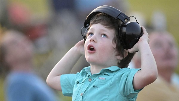 A young airshow enthusiast keeps his eyes on the action while adjusting his headset during the night airshow at the Sun 'n Fun Aerospace Expo on April 14. Photo by Phelan M. Ebenhack.