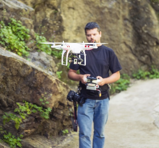 A man uses a handheld controller to fly a DJI Phantom quadcopter. iStock photo.