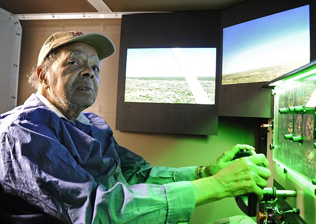 World War II Tuskegee Airman Lt. Floyd Collins, who trained in Mustang P-51 airplanes at South Dakota's Rapid City Army Air Base, concentrates on flying a Redbird FMX flight simulator at the Montgomery County Airpark. Photo by David Tulis/AOPA.