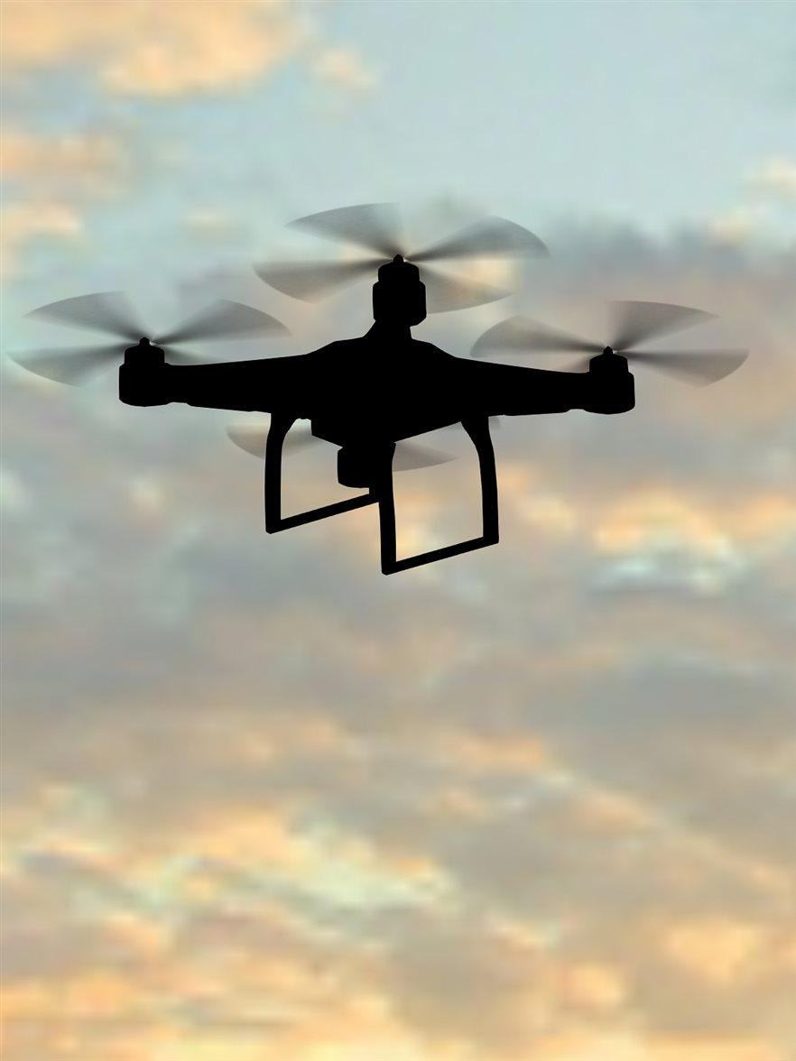 man operating of flying drone quadrocopter at sunset