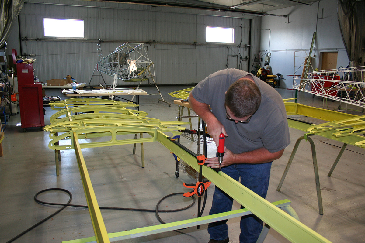 Baker Air Service's John Anderson installs Wipaire's 2,000-pound gross-weight increase kit on the wings.