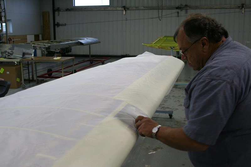 Baker Air Service Owner Roger Meggers works on covering the Super Cub's left wing. Photo courtesy of Baker Air Service.