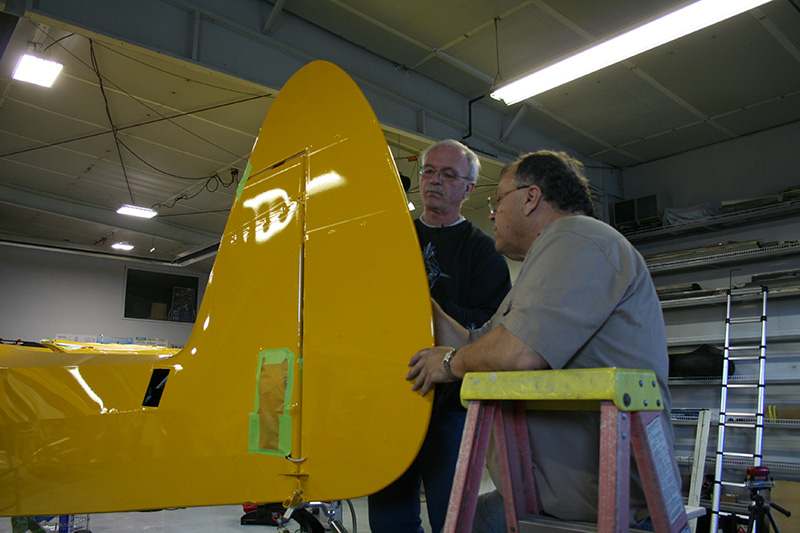 Detailing expert Don Buerkle and Baker Air Service's Roger Meggers prepare to put on the AOPA Sweepstakes Super Cub's unique tail art.
