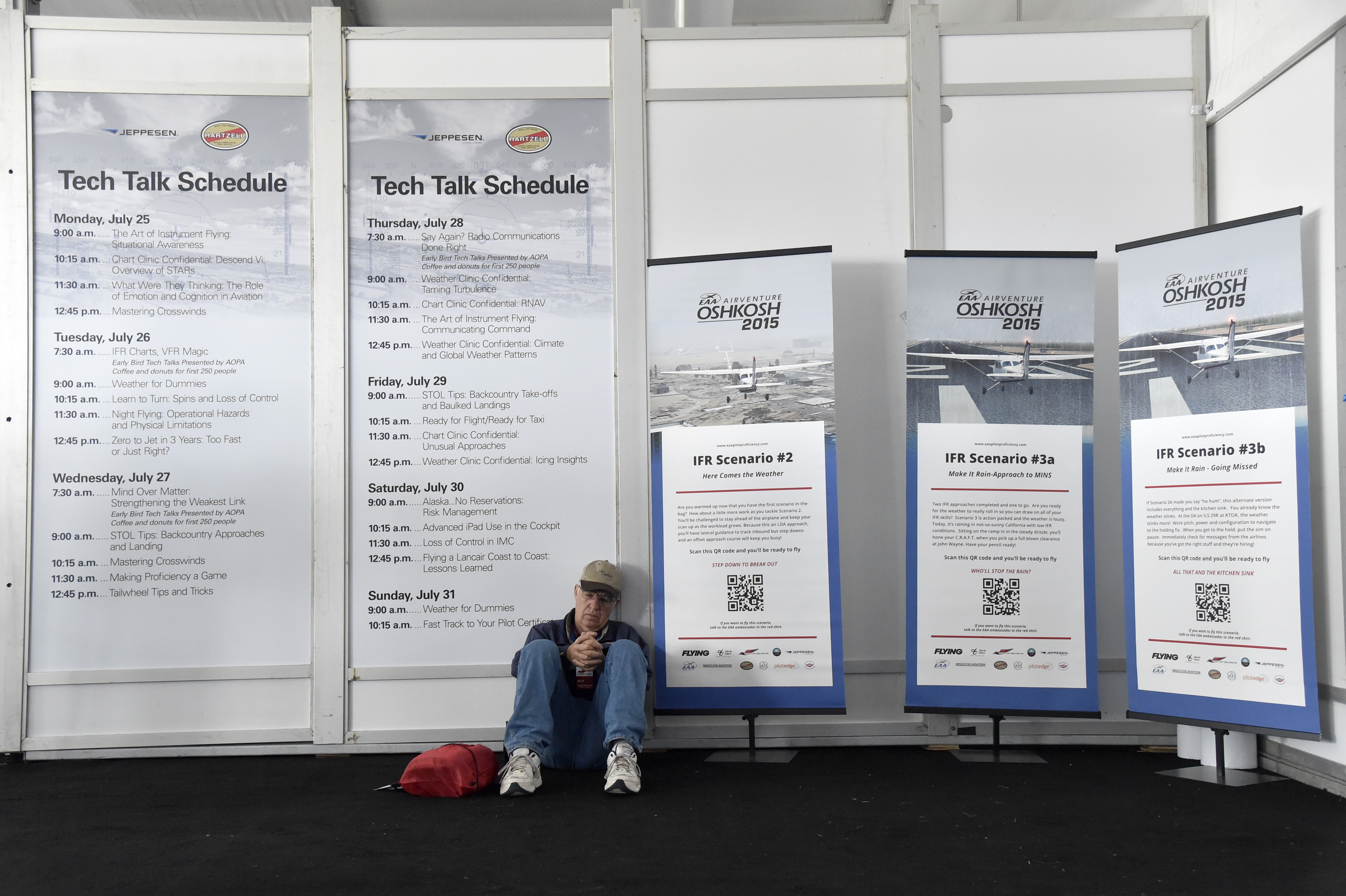 A pilot waits near Tech Talk posters in the Pilot Proficiency Center during EAA AirVenture. Photo by David Tulis.