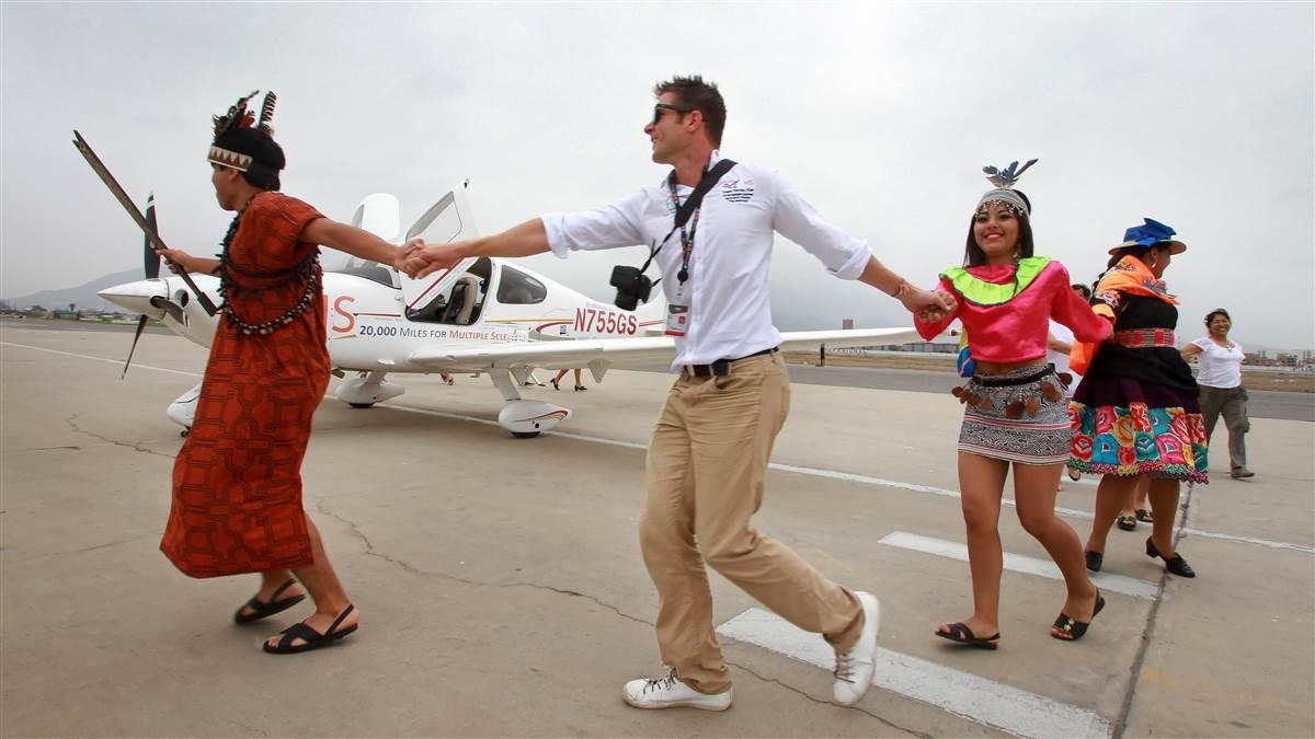 Fly for MS pilot Tomas Vykruta joins Peruvians for a dance next to his parked Cirrus during a circumnavigation flight of South and Central America. Photo courtesy of FlyforMS.org.