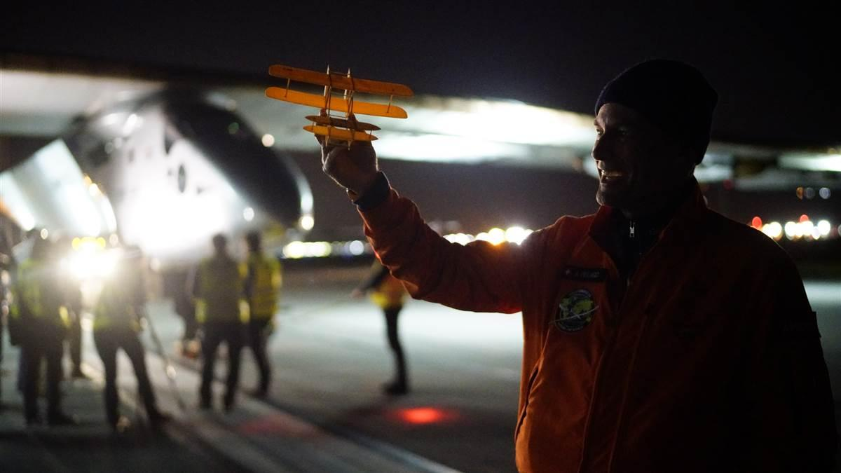 Solar Impulse co-founder Bertrand Piccard holds up a model of the Wright Flyer as André Borschberg disembarks in Dayton, Ohio, May 21. Photo courtesy of Solar Impulse.