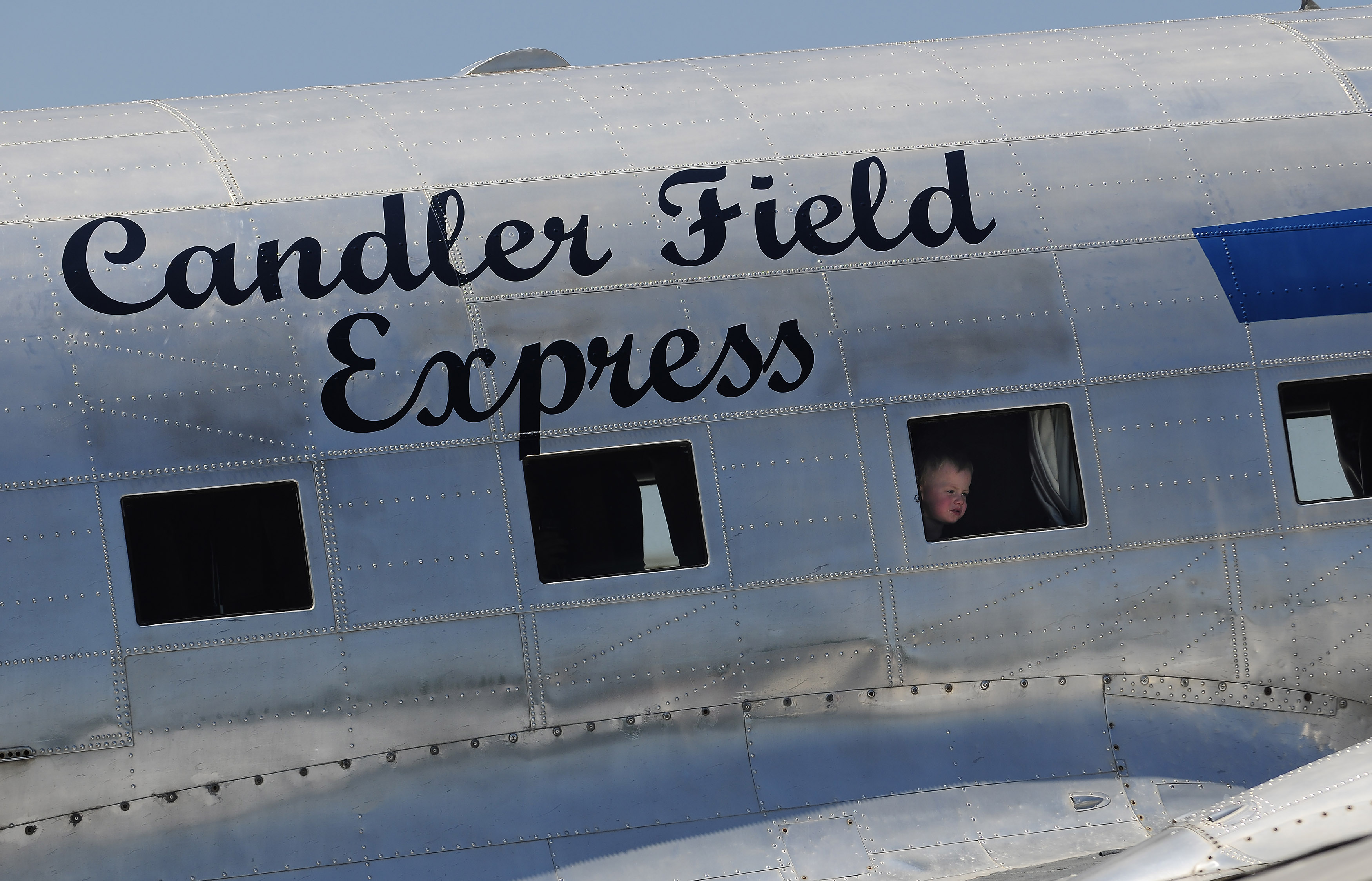 The 'Candler Field Express' DC-3 owned by Ron Alexander provides an interesting view for a young aviator during Peach State Aerodrome's 2011 Vintage Day celebration in Williamson, Georgia. Photo by David Tulis.