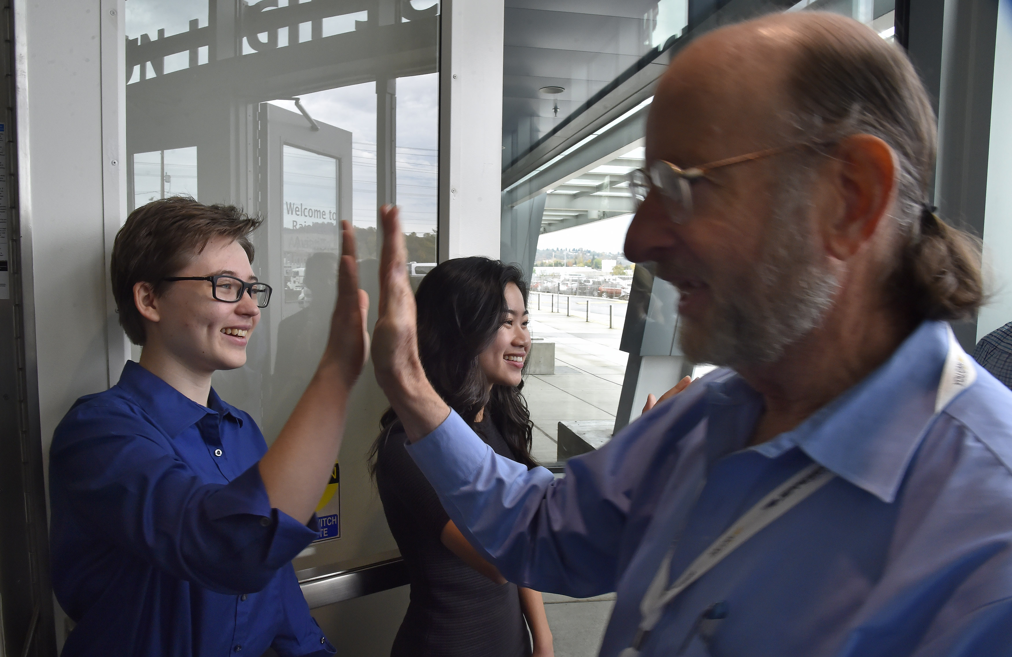 Raisbeck Aviation High School students greet AOPA High School Symposium attendees with a high-five during a tour of the facility in Seattle, Nov. 7. Photo by David Tulis.