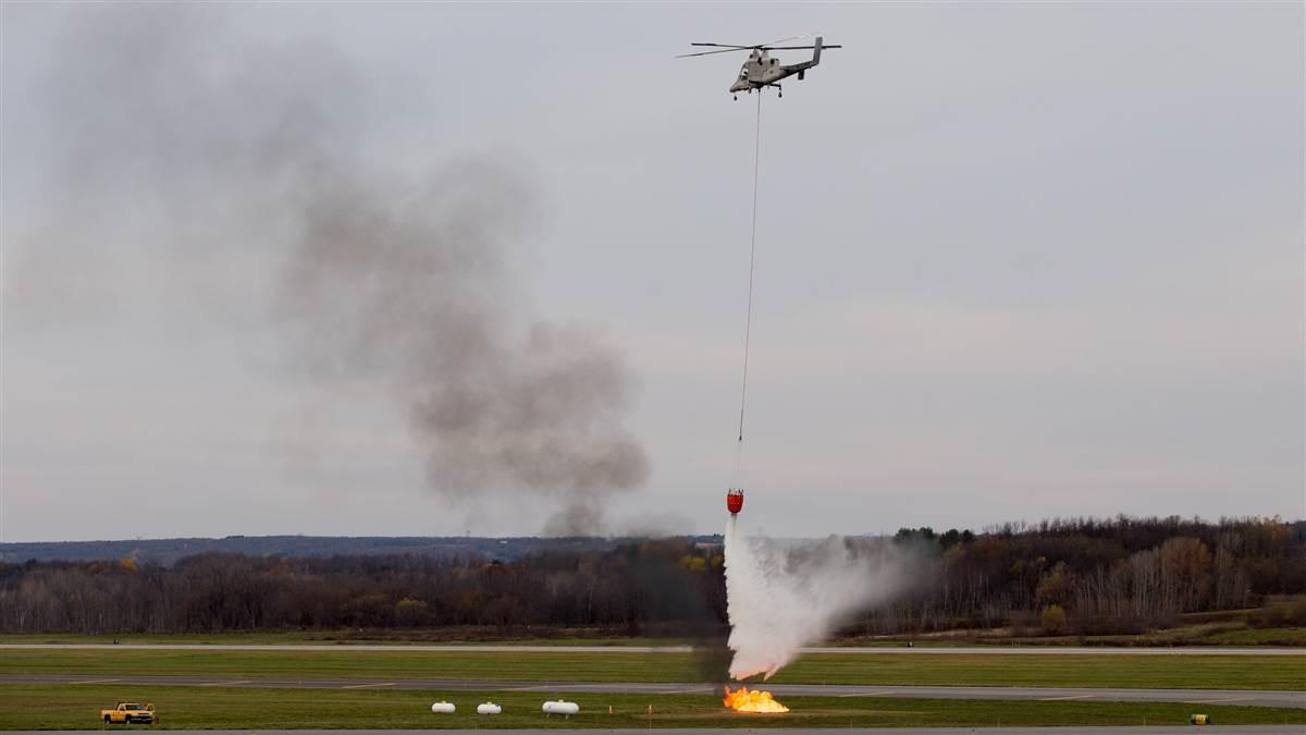 A K-MAX helicopter drops water on a propane-fueled fire during a demonstration at Griffiss Inernational Airport in Rome, New York Nov. 8. Jim Moore photo.