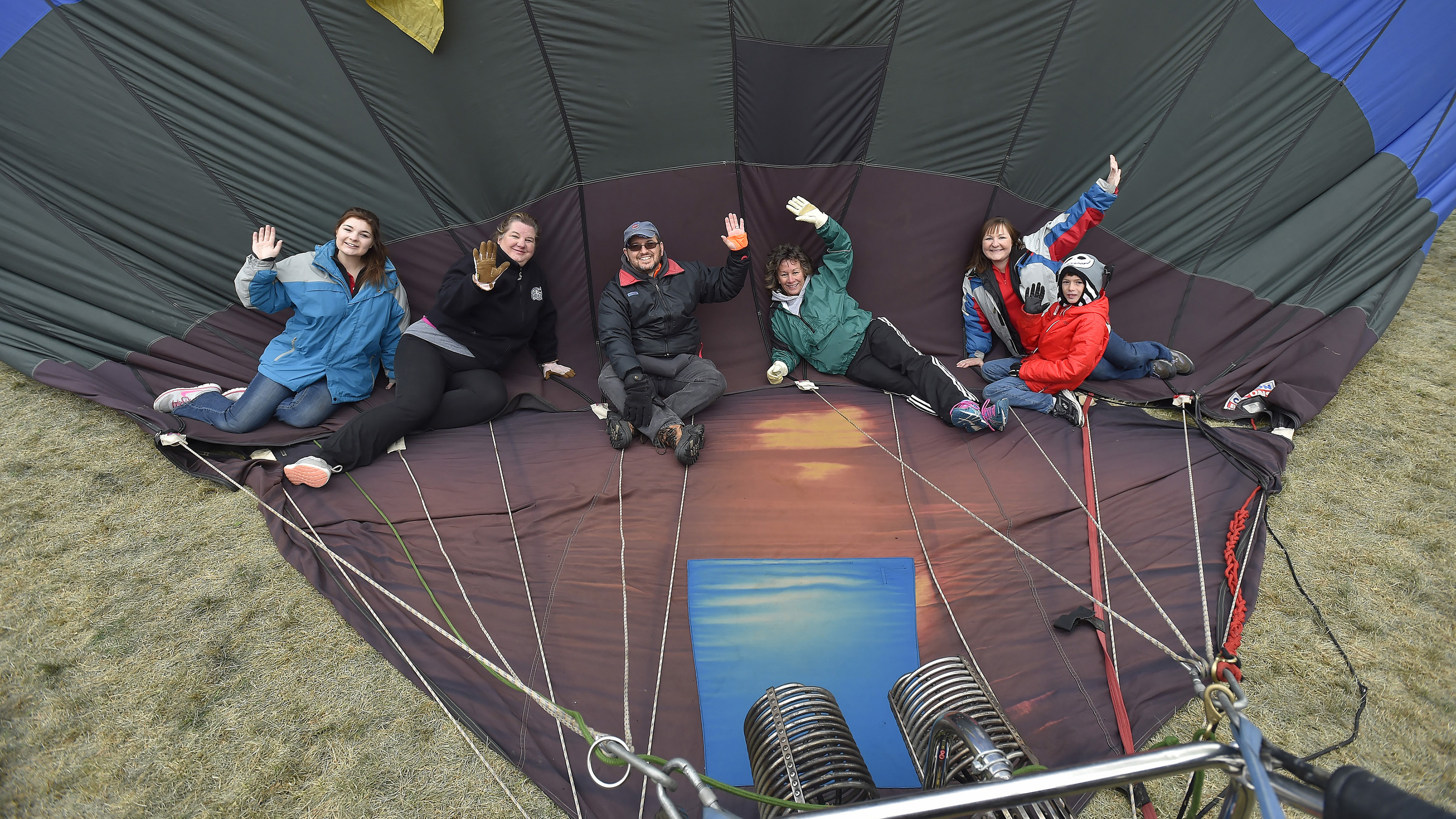 Montana balloonist Colin Graham's crew members wave while they trap hot air in the envelope behind them during the Albuquerque International Balloon Fiesta, Oct. 8. Photo by David Tulis.