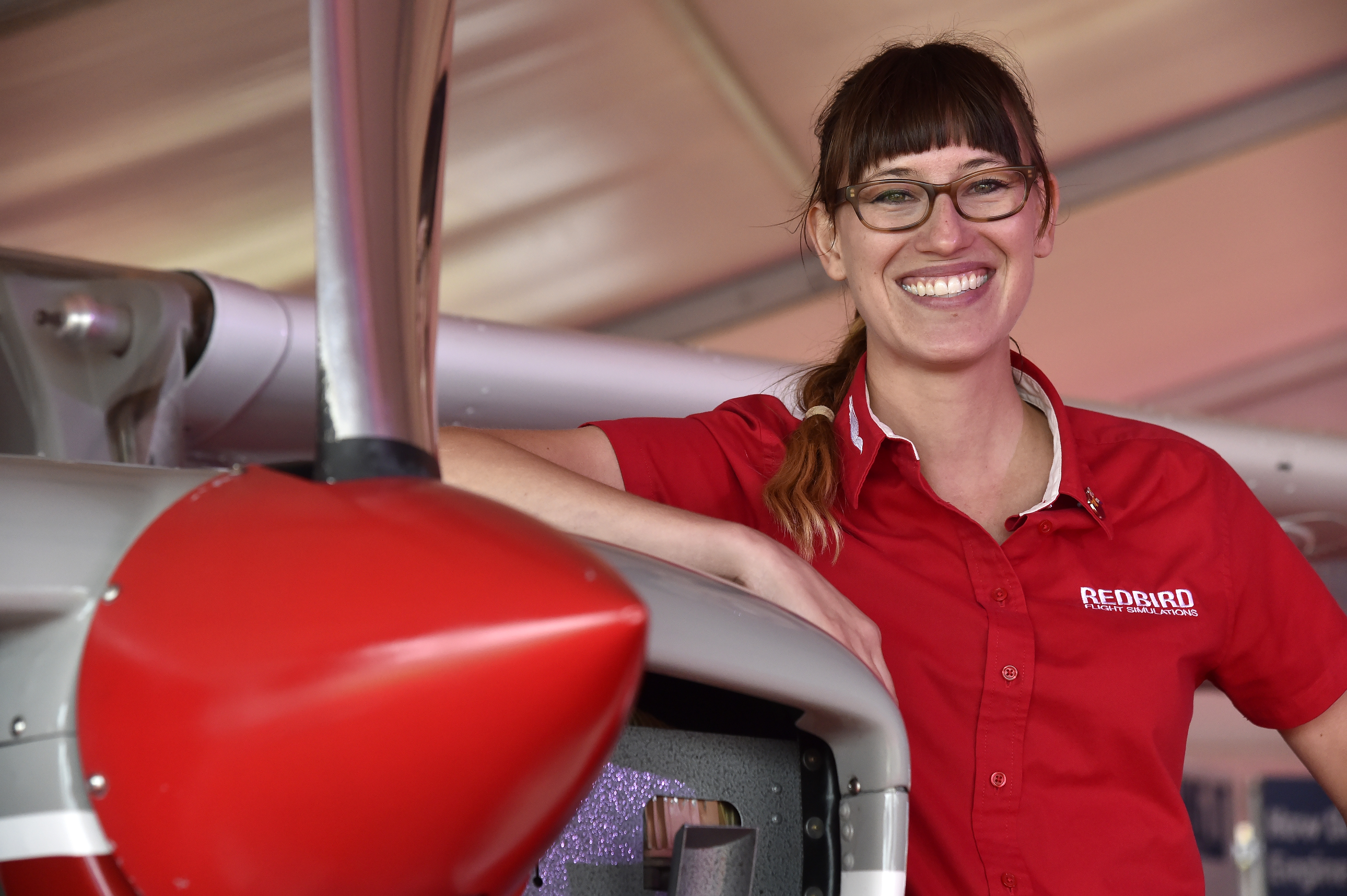 Redbird's Winging It video host Brittney Miculka's next challenge involves steering more than 100 flight instructors, educators, and flight school managers through Redbird Flight Simulations' annual Migration conference in Texas. Miculka is shown at the Redbird booth during EAA AirVenture 2016 at Wittman Regional Airport in Oshkosh. Photo by David Tulis.
