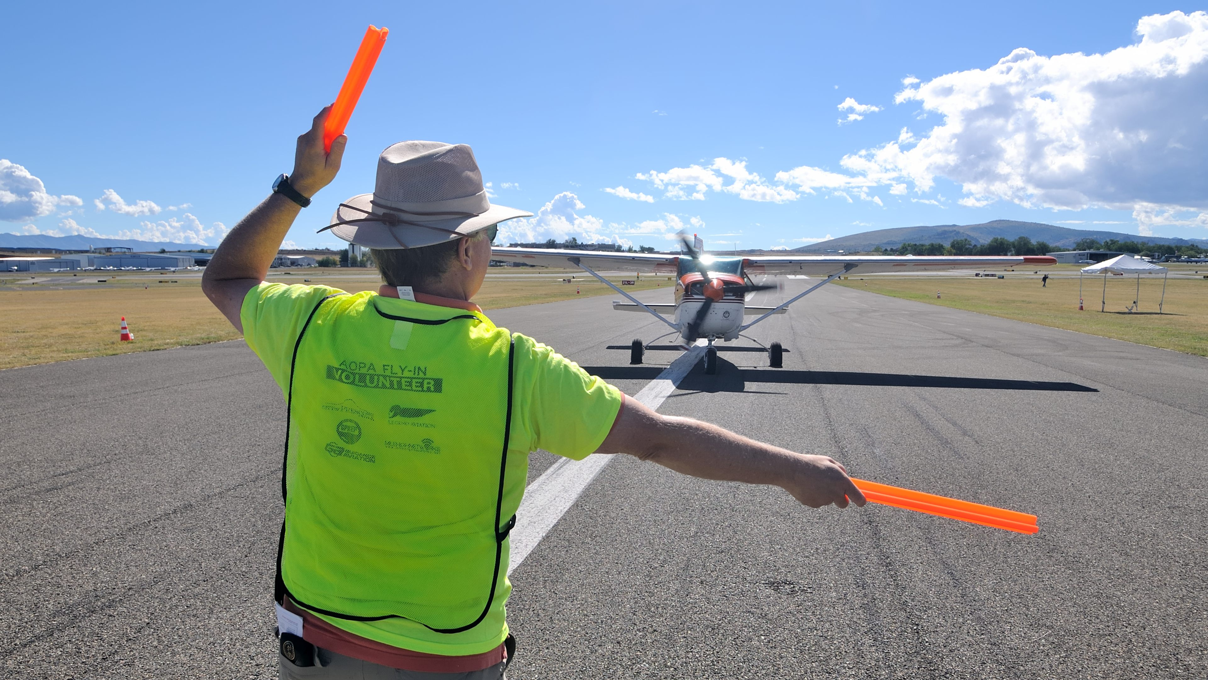 Volunteer Jerry McMillan of Prescott, Arizona, marshals an aircraft into the camping area at AOPA's Prescott Fly-In. Photo by Mike Collins.