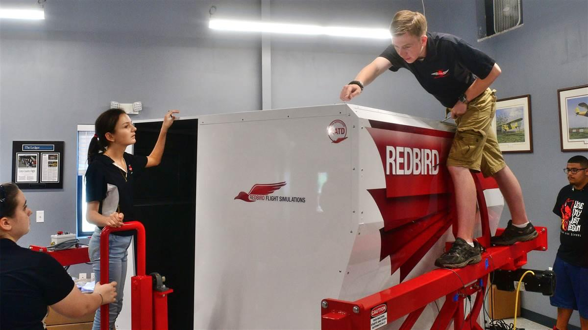 Members of the Lakeland Aero Club, a not-for-profit high school flying club in Lakeland, Florida, build a Redbird FMX simulator. Photo by Mike Collins.