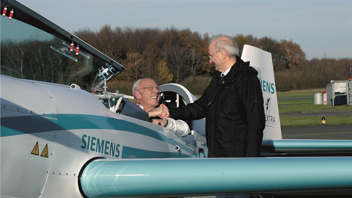 Frank Anton (right), who heads eAircraft for Siemens, congratulates pilot Walter Extra, who broke the world time-to-climb record on November 25. Photo courtesy of Siemens.