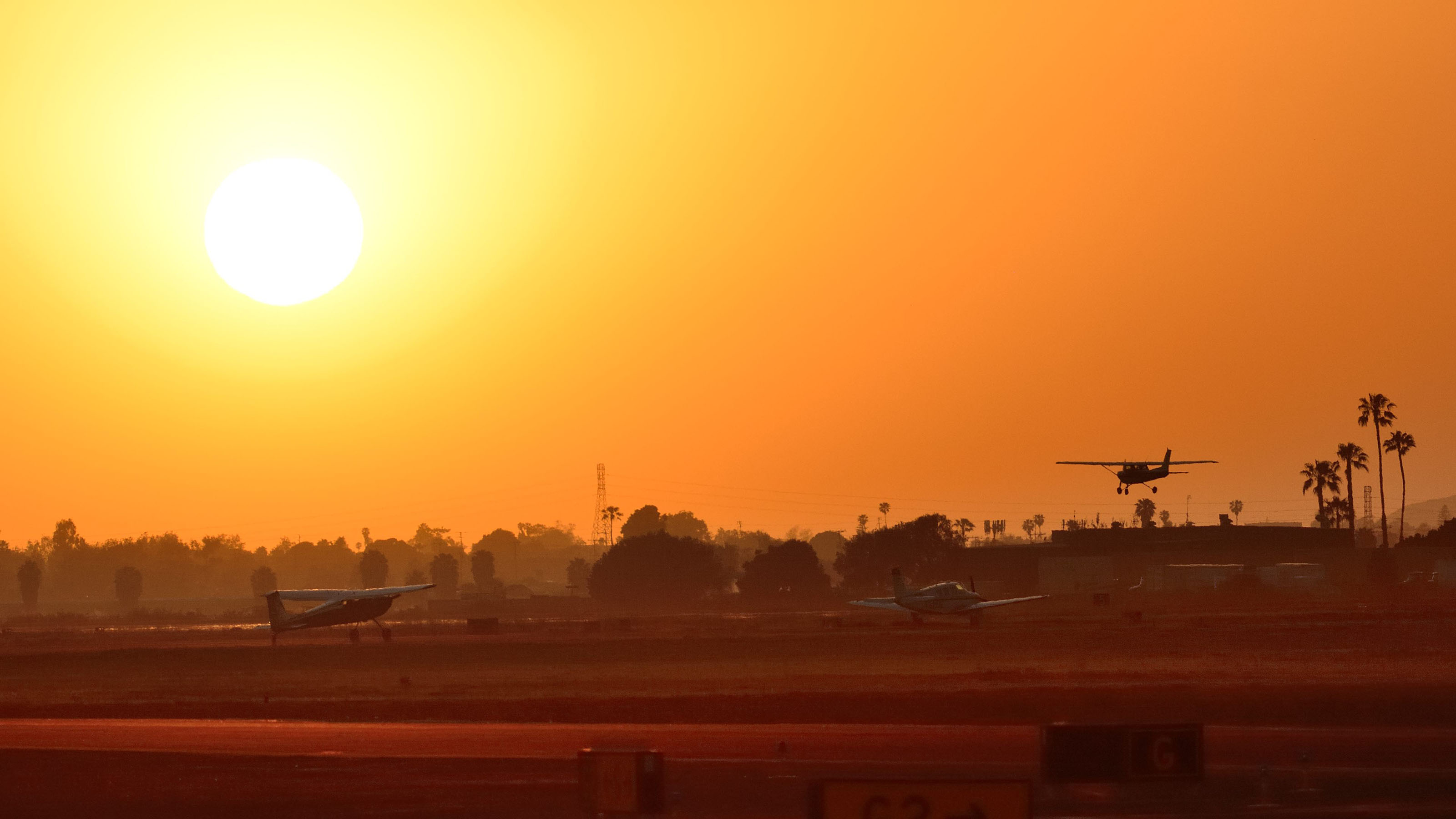As the sun sets at Camarillo Airport on Friday night, a Cessna lands while two airplanes wait to depart. Photo by Mike Collins.