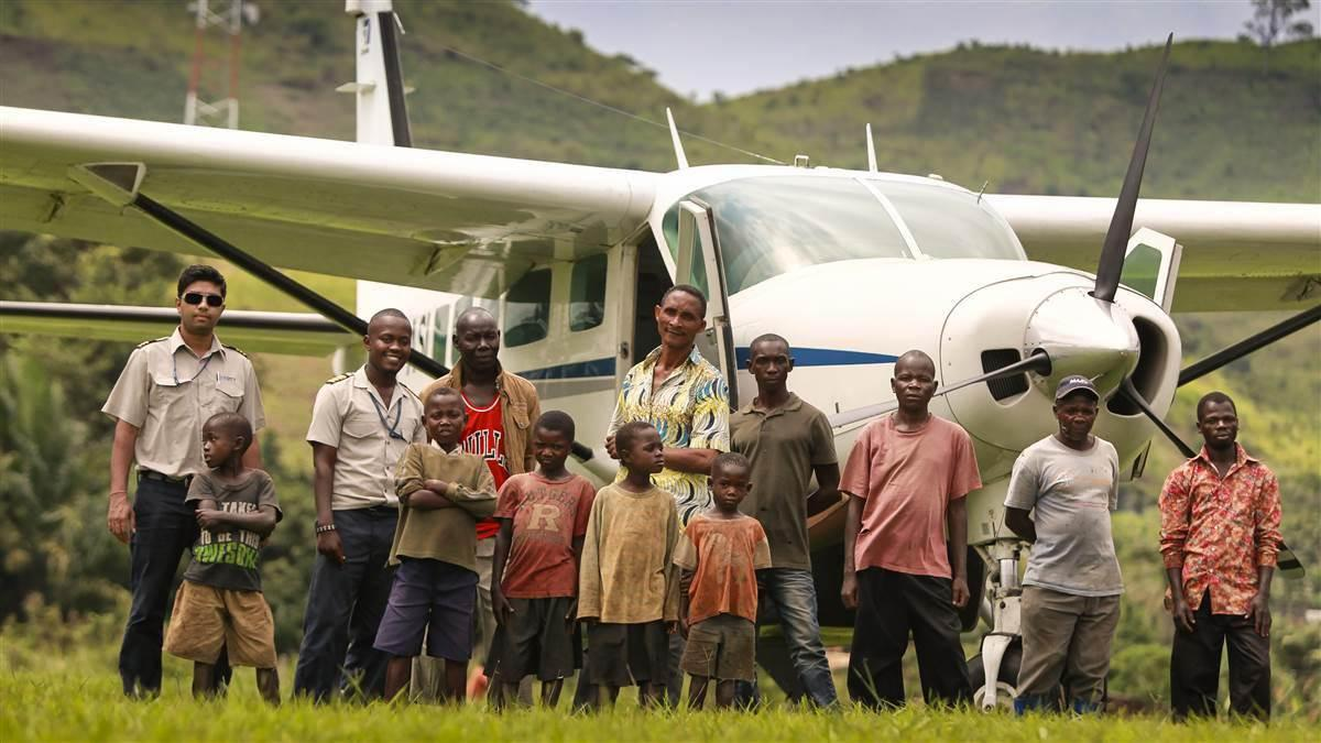 Air Serve International pilots are surrounded by a welcoming and curious group of villagers. Photo by Chris Rose.