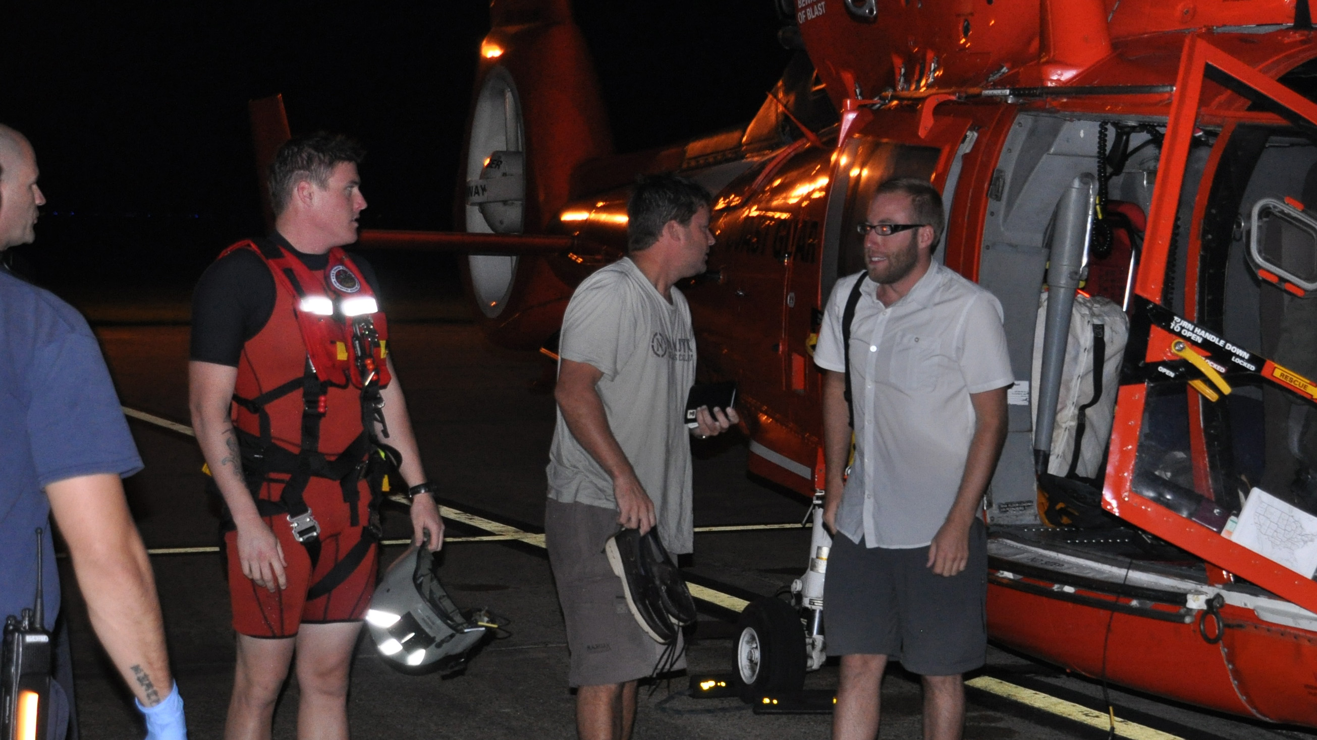 Pilot Theodore R. Wright III, far right, and passenger Raymond Fosdick, second from right, were rescued by the U.S. Coast Guard after ditching in the Gulf of Mexico. Both men now stand accused of fraud. Coast Guard photo.