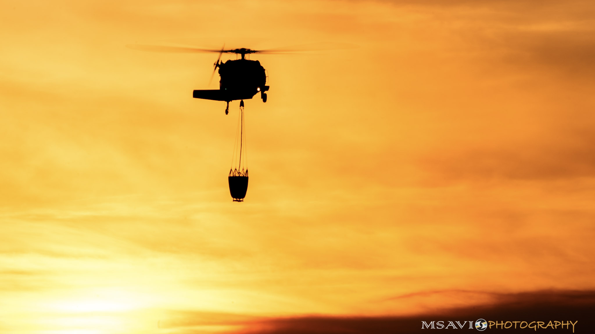 The sun frames a helicopter carrying a bucket during firefighting operations based at California's Santa Paula Airport. Photo by Mike Salas, MSAVI Photography and Focal Flight.