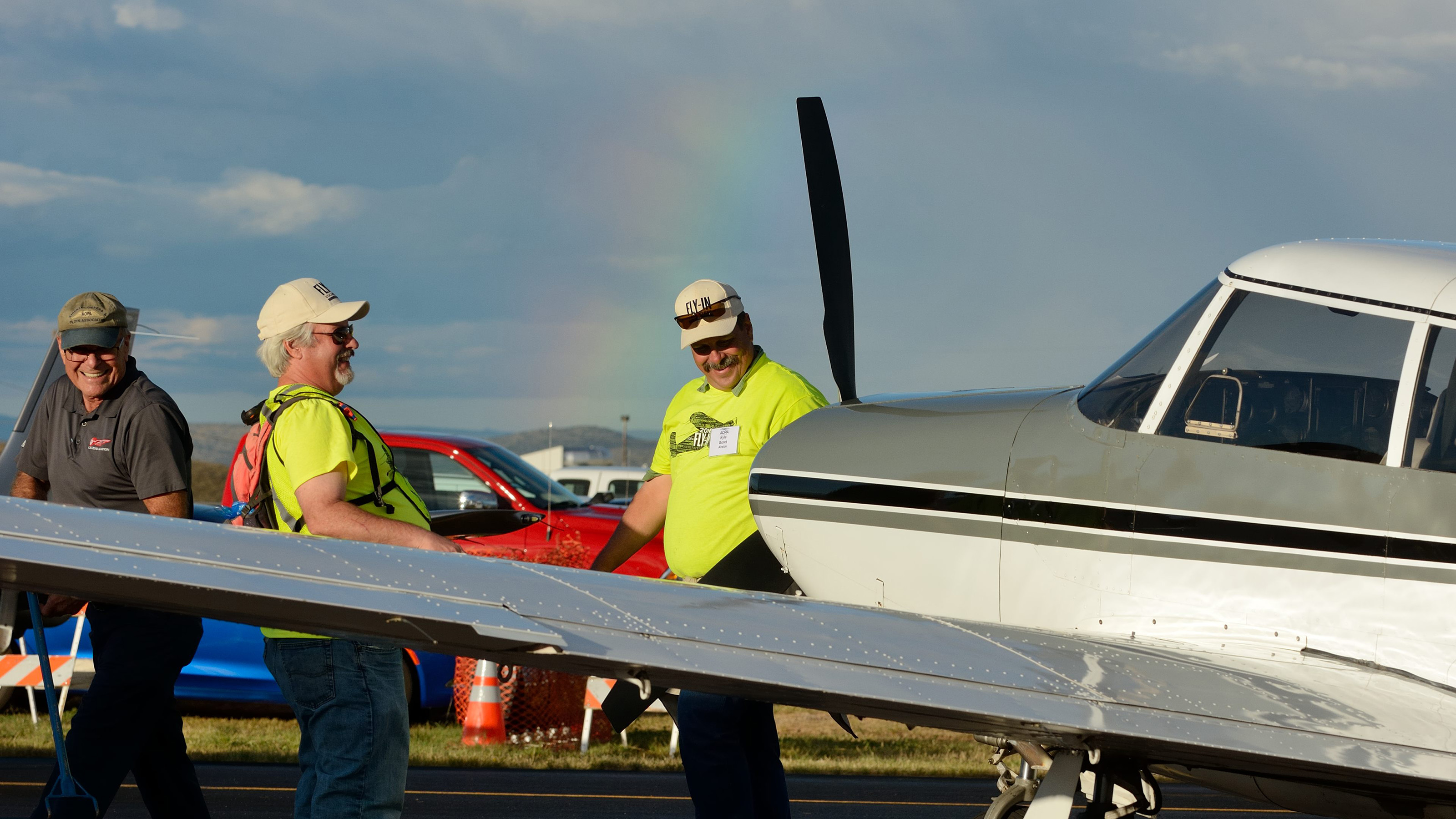 Airside volunteers share a laugh after positioning a Piper Comanche in the static display. A rainbow gives evidence of an afternoon rainshower. Photo by Mike Collins.
