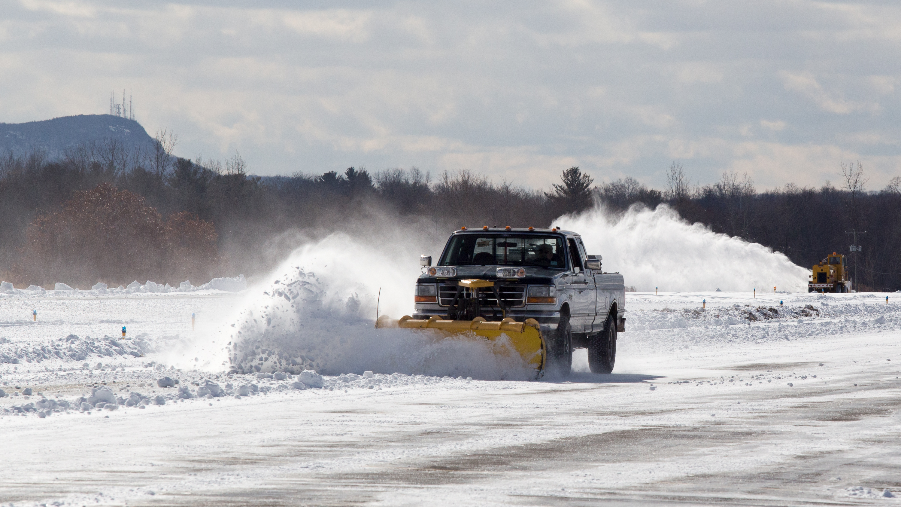 Airport manager Bill O'Leary plows with a pickup while one of his employees clears the runway with an SMI Snowmaster on Feb. 10. Jim Moore photo.