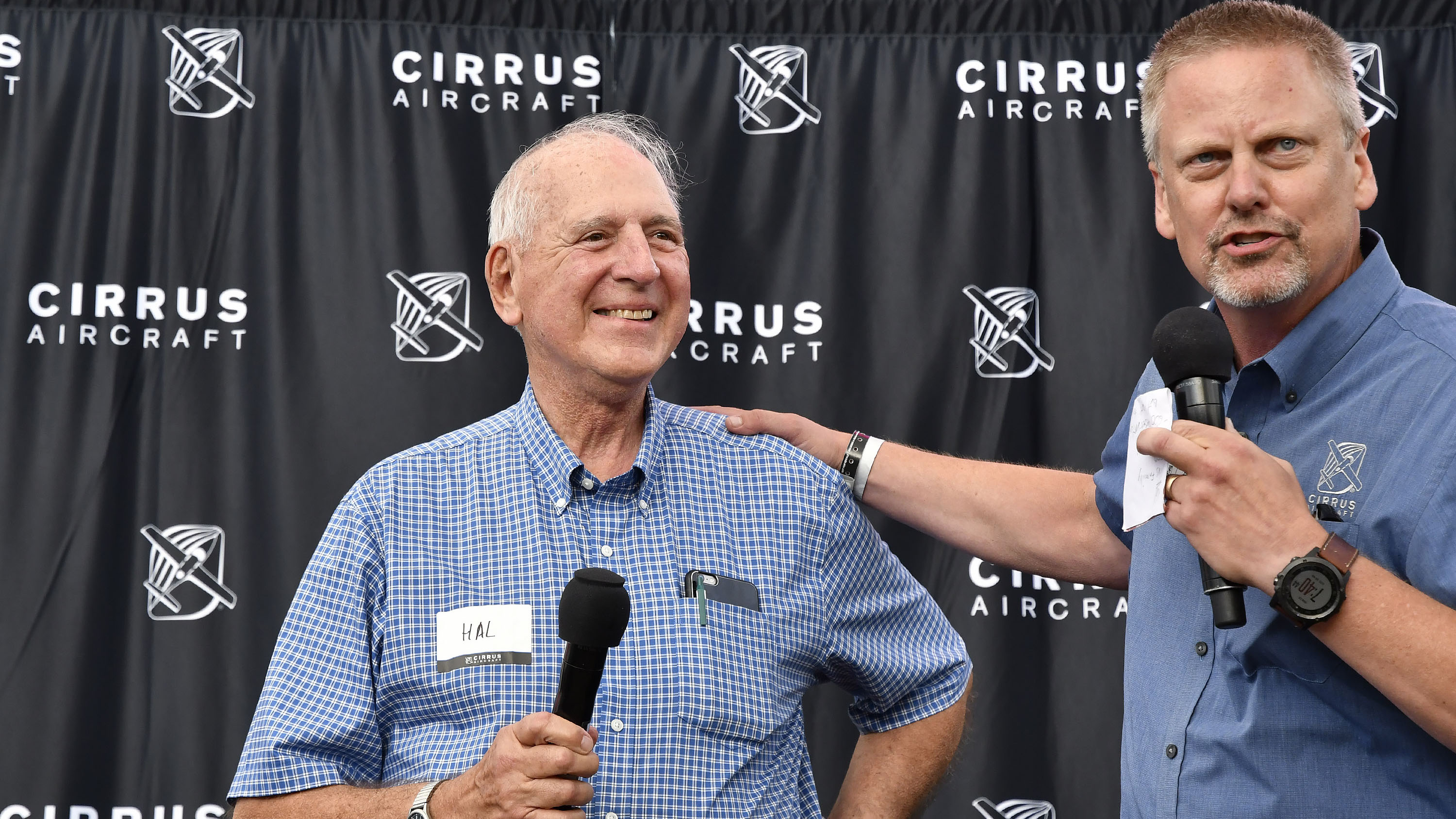 Sporty's Pilot Shop founder Hal Shevers and Cirrus co-founder Dale Klapmeier announce an auction for Shevers' Cirrus Vision Jet delivery position during EAA AirVenture at Wittman Regional Airport in Oshkosh July 23. Photo by David Tulis.