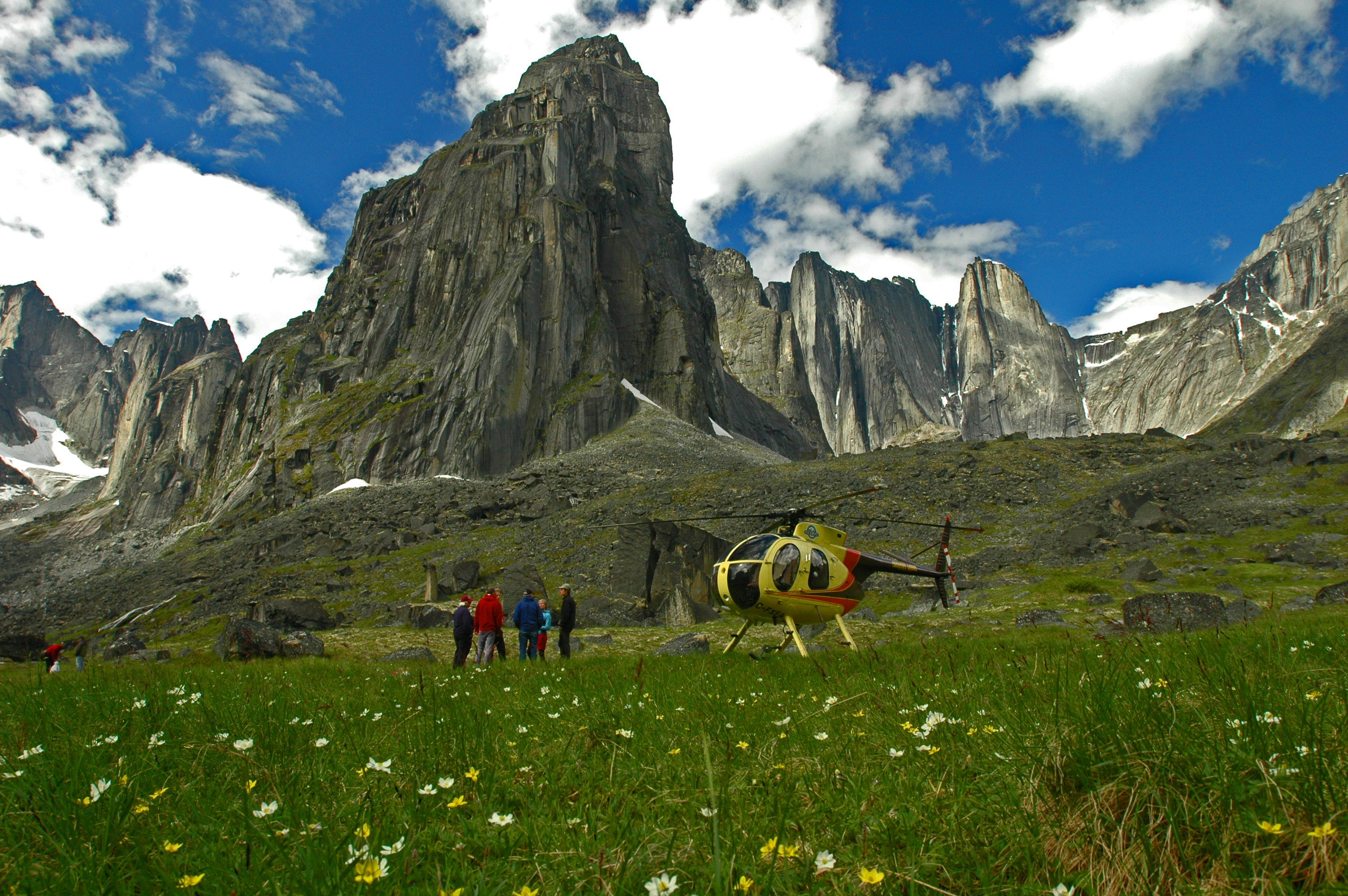 These adventurers have landed on a meadow inside Nahanni National Park, via the Hughes 500 helicopter owned and flown by Warren LaFave of the Inconnu Lodge. Behind them, near-vertical granite cliffs rise several thousand feet, forming what is known as the 'Cirque of the Unclimbables.'  Mountain climbers come here from all over the world to test their skills. Photo courtesy Inconnu Lodge.