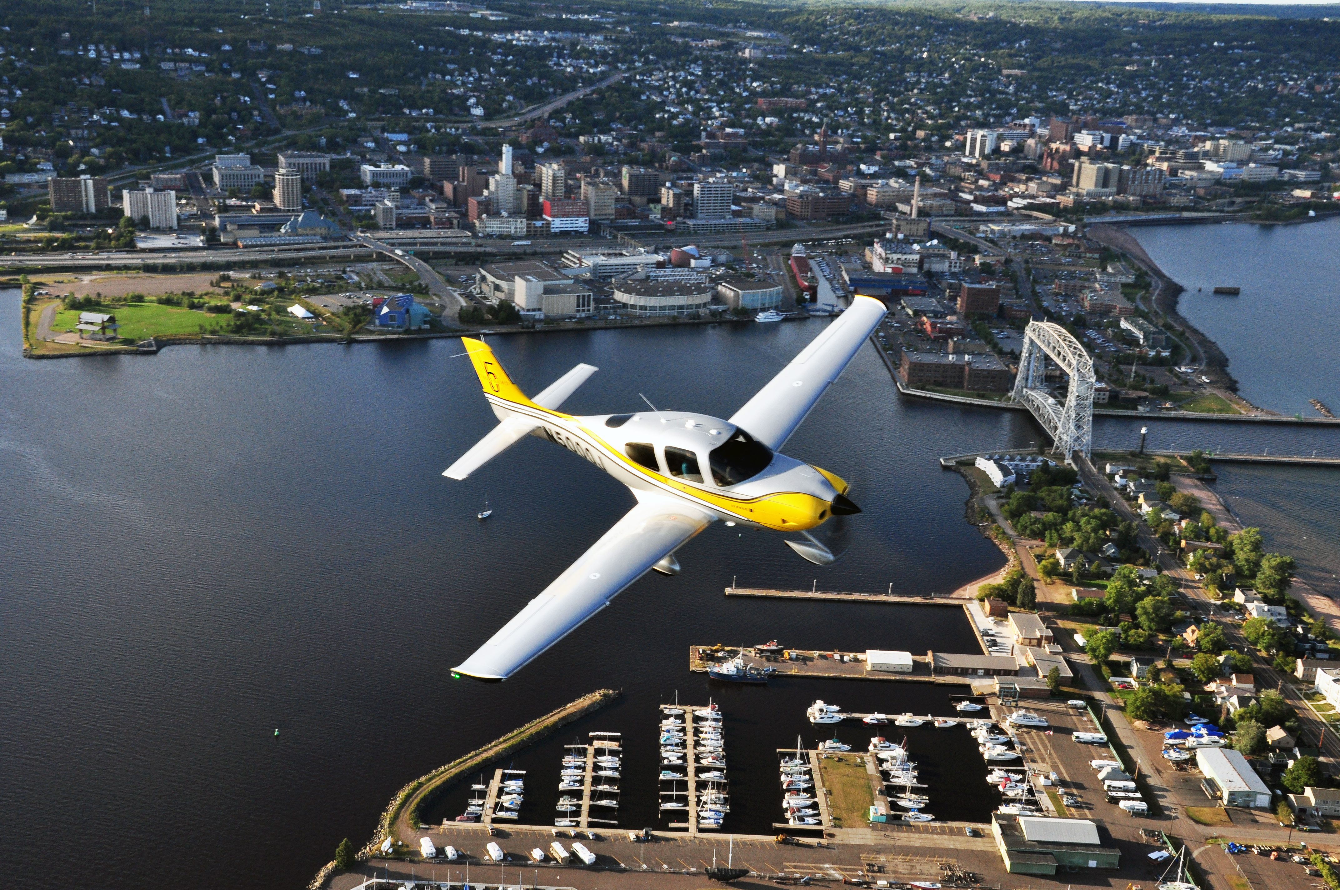 A Cirrus flies over the marina at north end of Minnesota Point. The aerial lift bridge connects Minnesota Point to Canal Park, and, beyond it, Duluth proper. Visitors can tour the Duluth Cirrus factory and see production of all three piston lines, plus the new Vision jet. Photo courtesy Cirrus Aircraft.