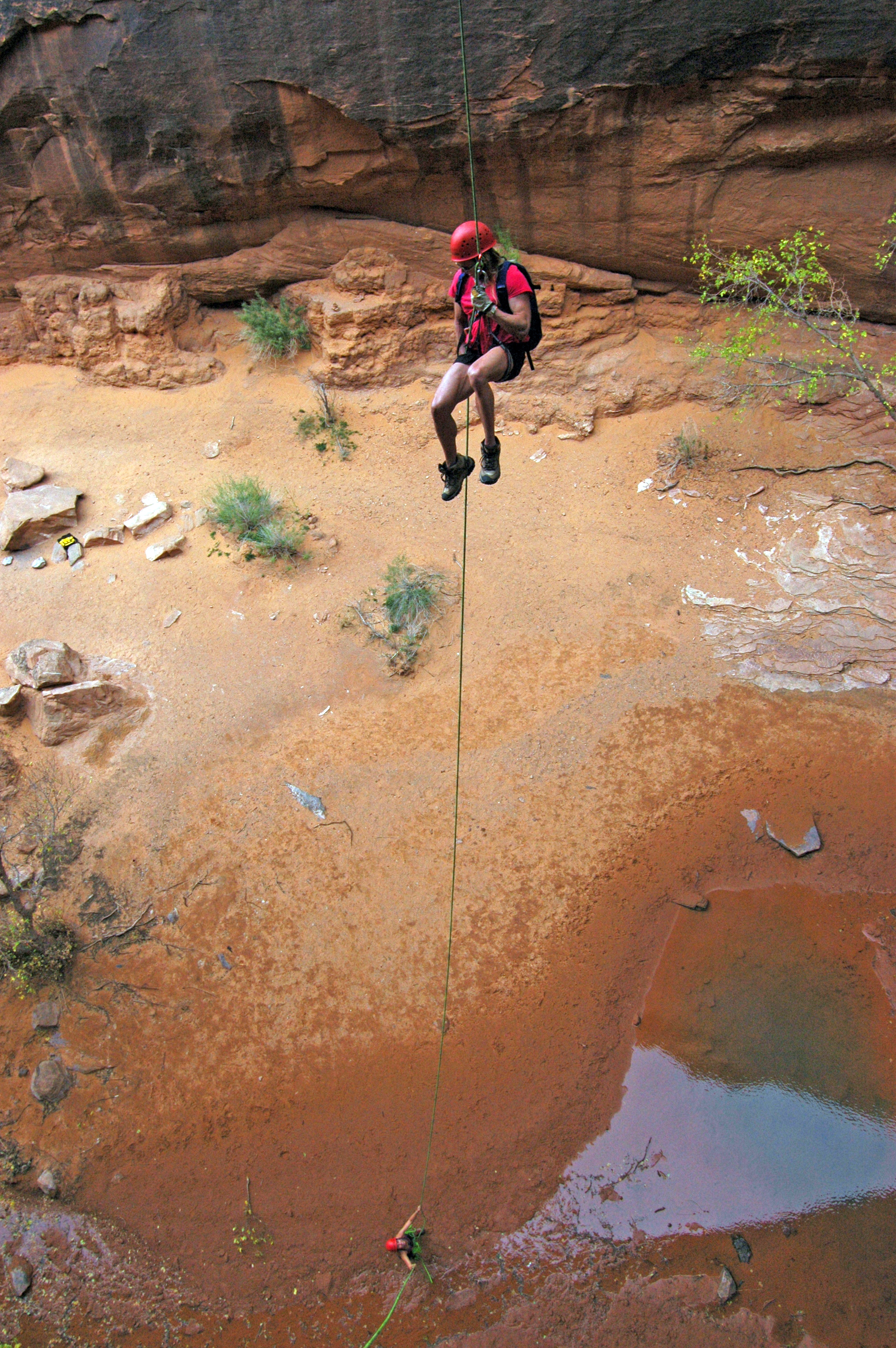 The author rappels off Morning Glory Arch, just south of Arches National Park. Morning Glory is about 100 feet high, with a span of 243 feet. Photo by Herb Crimp, Desert Highlights.