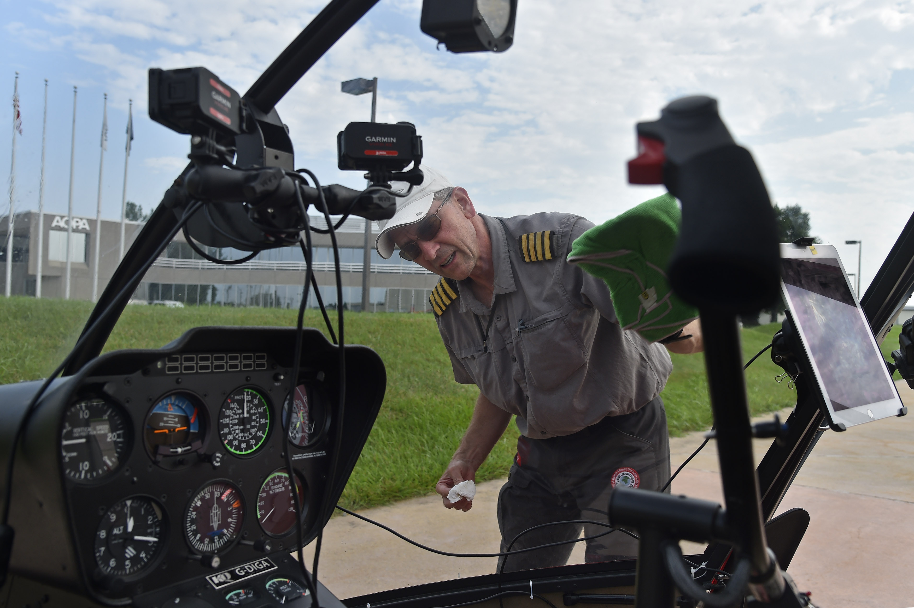 British helicopter pilot Peter Wilson cleans the windscreen during a stop at AOPA headquarters in Frederick, Maryland, as they entered the final quarter of a world-spanning flight in a Robinson R-66. Photo by David Tulis.