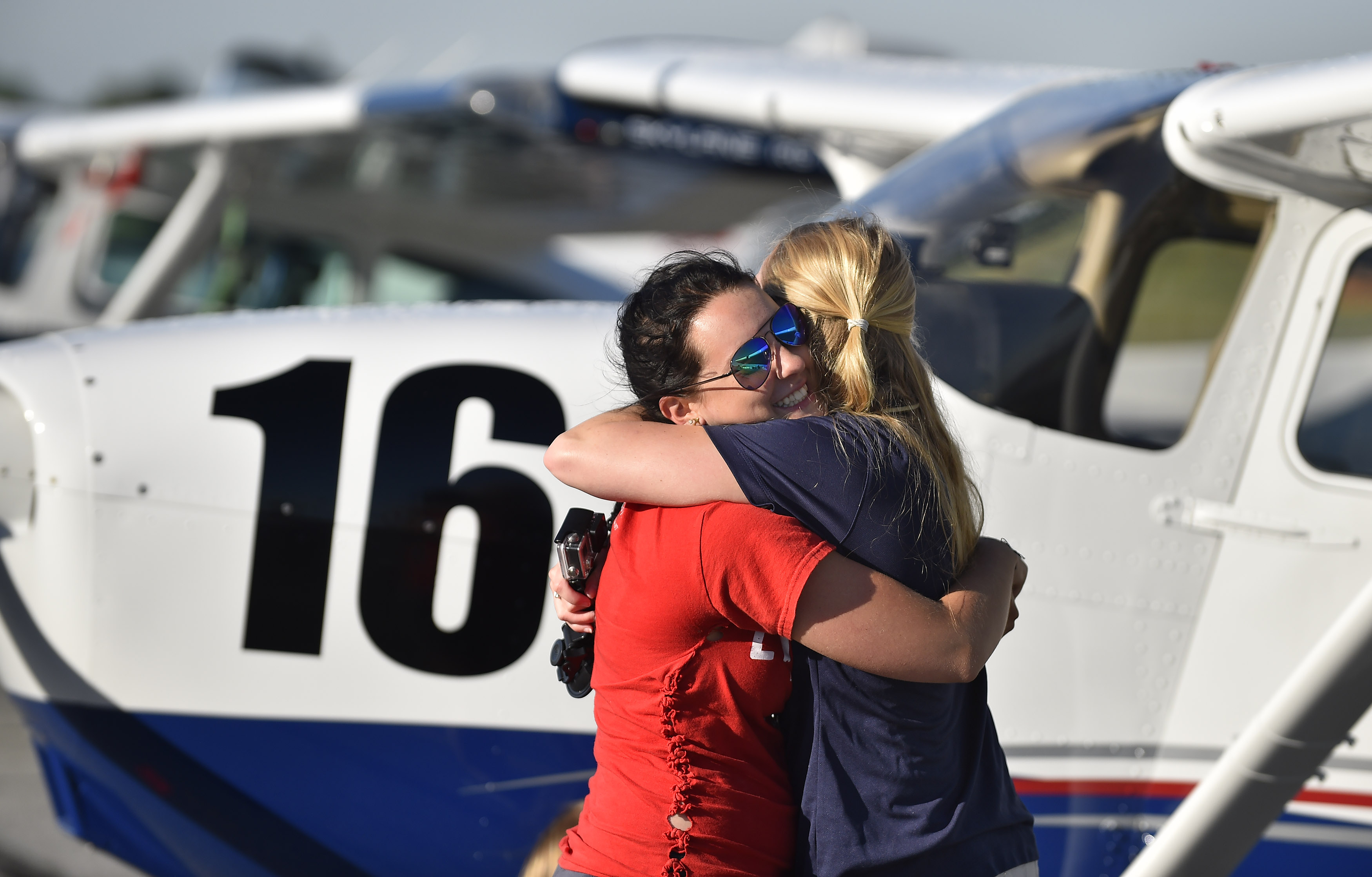 Olivia Fuller hugs Liberty University Air Race Classic competitor Allie Grubb at the start of the four-day, 14-state all-female event at Frederick Municipal Airport in Frederick, Maryland, June 20. Photo by David Tulis.