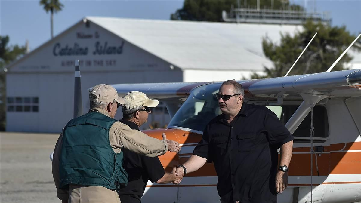 Cessna pilots Bob Lange, Mike Jesch, and Darrin Smith greet each other at Smith's Cessna 150. Smith removed a seat and slept in the Cessna rather than a tent. Photo by David Tulis.