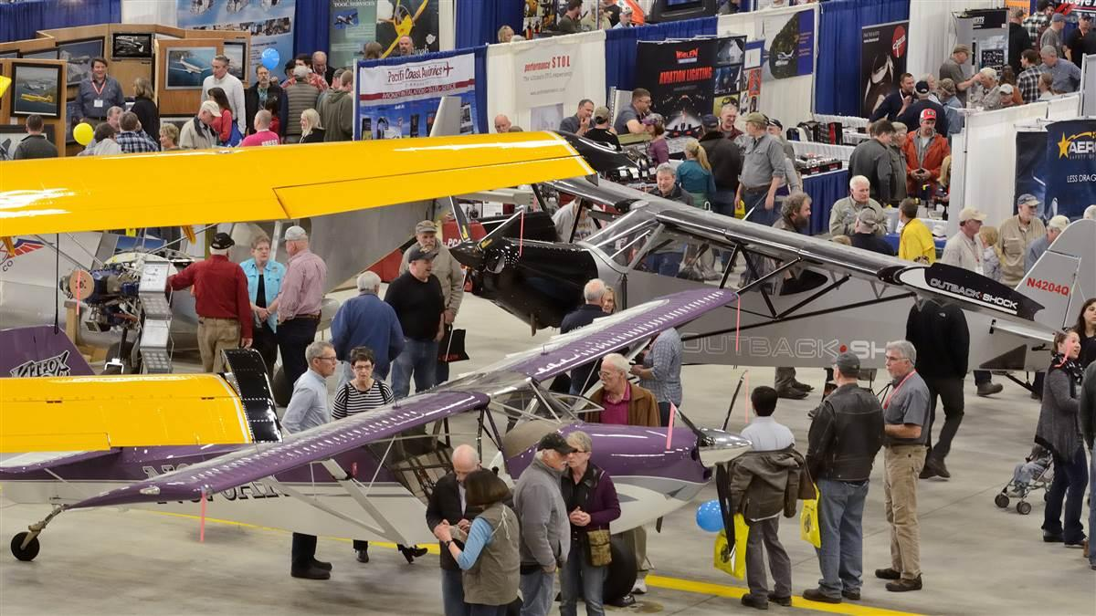 A purple-and-white Kitfox fit easily beneath the wing of a Quest Kodiak on amphibious floats, inside the Great Alaska Aviation Gathering's exhibit hall--a FedEx maintenance hangar at Ted Stevens Anchorage International Airport.